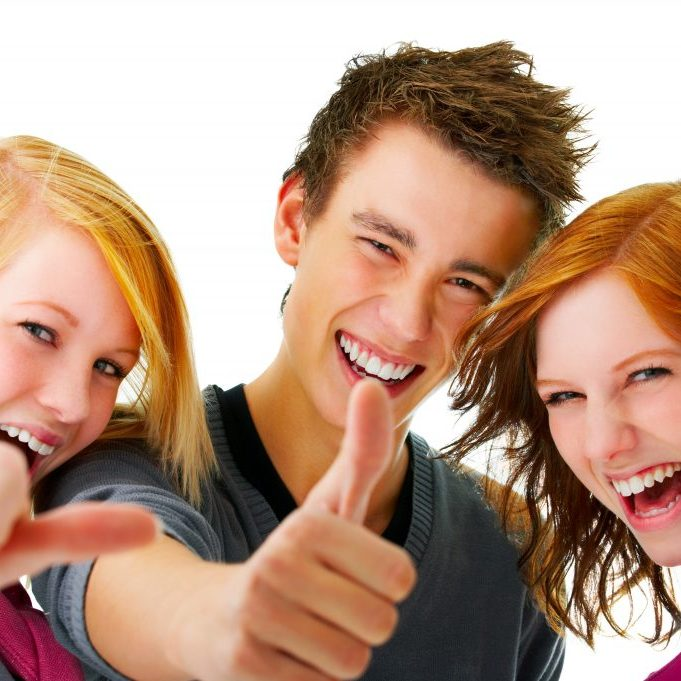 Portrait of three young teenagers laughing and giving the thumbs-up sign.